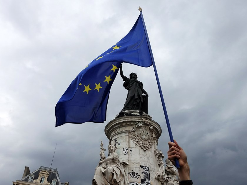 A demonstrator waves a European Union flag during a protest in solidarity with migrants at Place de la Republique in Paris on September 5, 2015, after the 'Pas en notre nom' (Not in our name) collective organized the event on social networks. Photo: AFP/Guillemtte Villemin