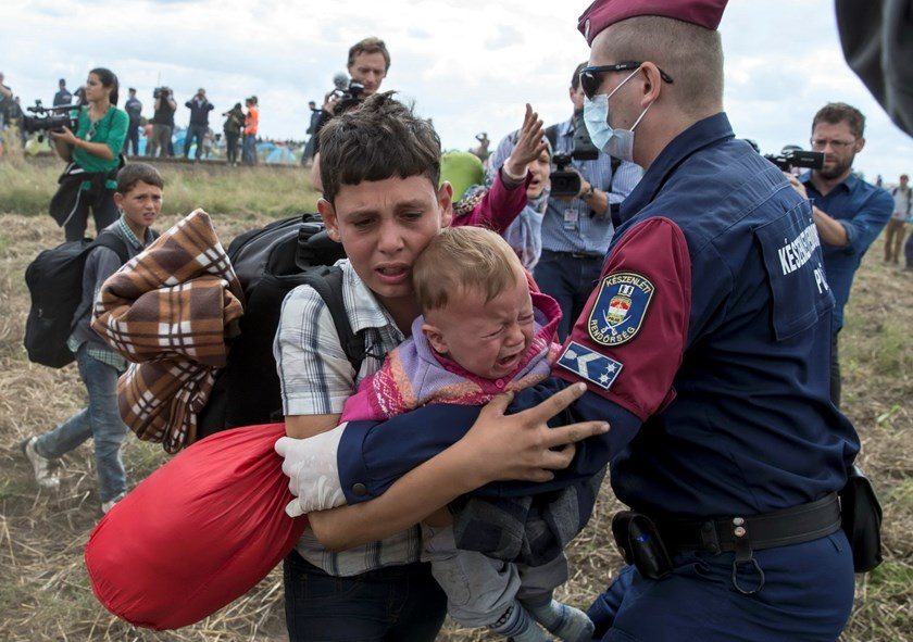 A Hungarian policeman attempts to stop a migrant carrying a baby to run from a collection point in Roszke village, Hungary, September 8, 2015. Photo: Reuters/Marko Djurica