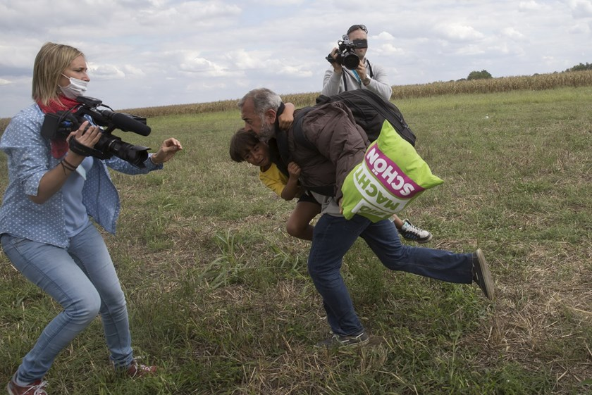 A migrant runs with a child before tripping on TV camerawoman Petra Laszlo (L) and falling as he tries to escape from a collection point in Roszke village, Hungary, September 8, 2015. Photo: Reuters/Marko Djurica
