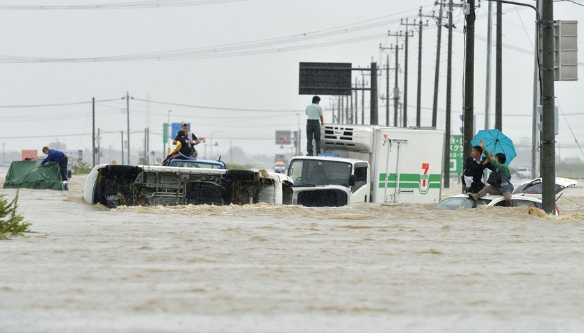 People wait for rescue on the roofs of cars as they are stranded on a road flooded by the Kinugawa river, caused by typhoon Etau in Joso, Ibaraki prefecture, Japan, in this photo taken by Kyodo September 10, 2015. Photo: Reuters/Kyodo