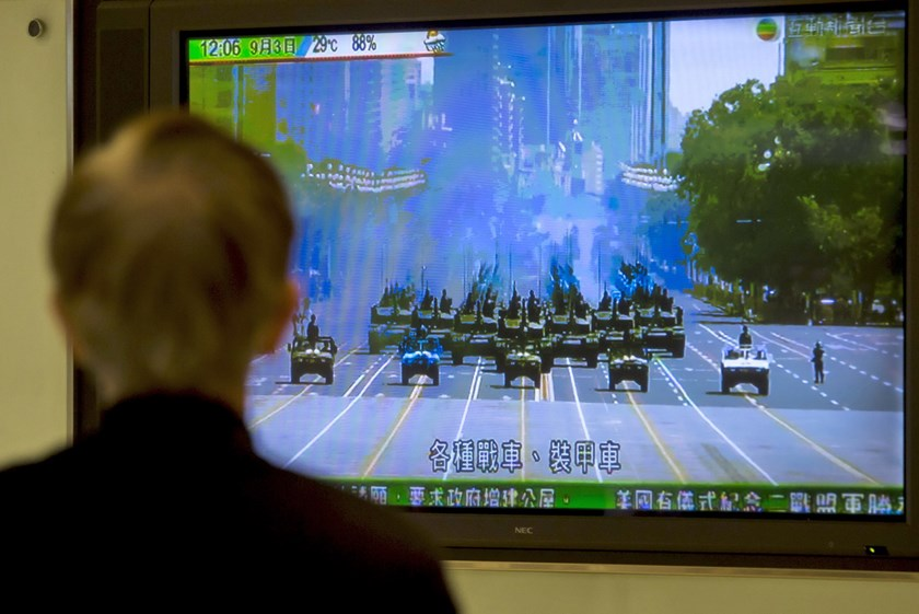 A man in Hong Kong watches a television showing Chinese People's Liberation Army (PLA) weaponries driving in formation past Beijing's Tiananmen Gate, China September 3, 2015. Photo: Reuters/Tyrone Siu
