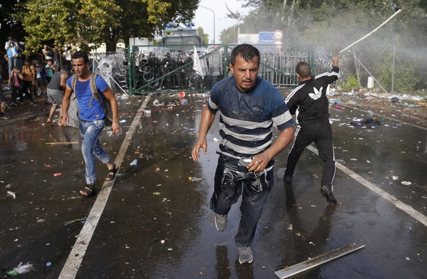 Migrants run as Hungarian riot police fires tear gas and water cannon at the border crossing with Serbia in Roszke, Hungary September 16, 2015. Hungarian police fired tear gas and water cannon at protesting migrants demanding they be allowed to enter from Serbia on Wednesday on the second day of a border crackdown. Photo: Reuters/Marko Djurica