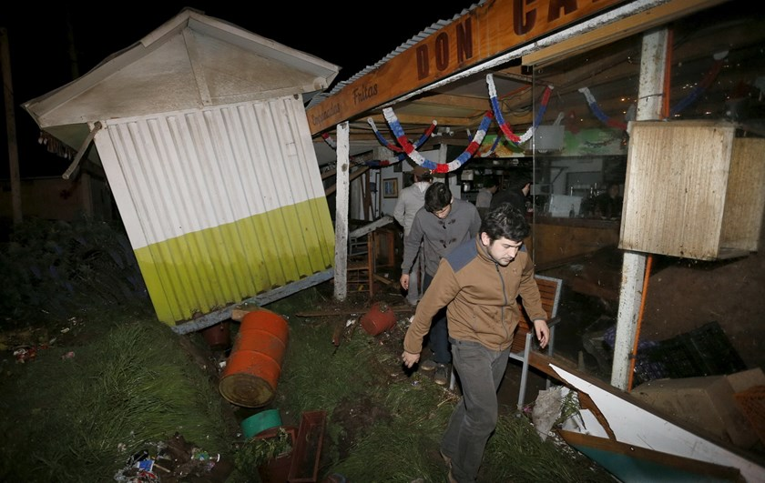 People recover items from a destroyed shop caused by the waves in Concon city September 16, 2015, after a mass evacuation of the entire coastline during a tsunami alert after a magnitude 8.3 earthquake hit off the coast of Chile on Wednesday. Photo: Reuters/Rodrigo Garrido