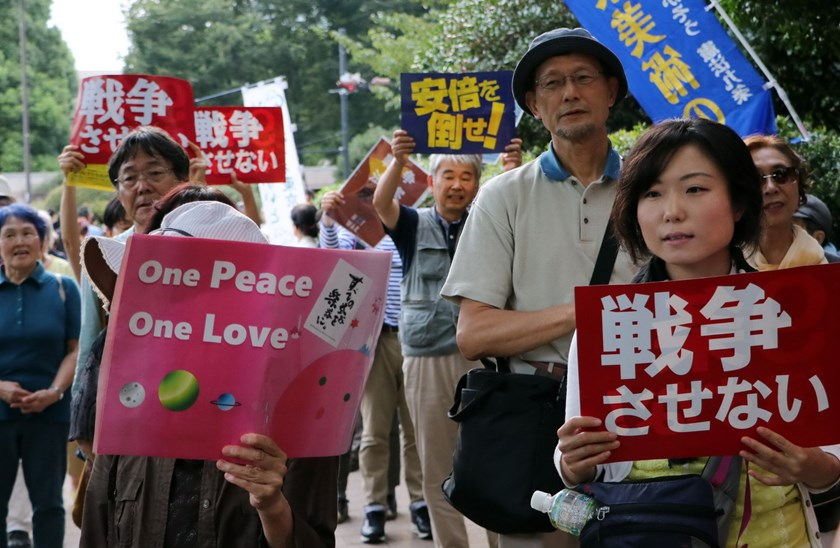 People hold placards to protest against Japan's Prime Minister Shinzo Abe's controversial security bills near the National Diet in Tokyo on September 19, 2015. Photo: AFP/Yoshikazu TSUNO