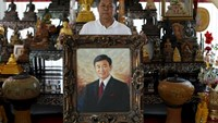 Red shirt movement leader Kwanchai Praipana poses with a photo of former PM Thaksin Shinawatra at his office in Udon Thani, Thailand, September 15, 2015. Photo: Reuters/Jorge Silva