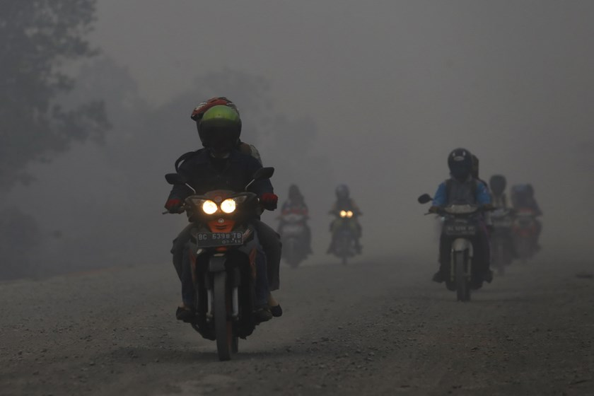 People ride their motorcycles as haze shrouds a street near Bagan Siapi-Api port, on the Indonesian island of Sumatra, September 19, 2015. Photo: Reuters/Beawiharta