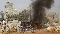 A man runs past a burning military vehicle at a base controlled by rebel fighters from the Ahrar al-Sham Movement, that was targeted by what activists said were Russian airstrikes at Hass ancient cemeteries in the southern countryside of Idlib, Syria October 1, 2015. Photo: Reuters/Khalil Ashawi