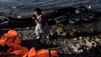 A young girl walks on the shore near orange life jackets and a deflated dinghy as refugees and migrants arrive on the Greek island of Lesbos after crossing the Aegean sea from Turkey on October 3, 2015. Photo: AFP/Aris Messinis