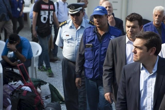 Greek Prime Minister Alexis Tsipras (R) and Austrian Chancellor Werner Faymann (not pictured) visit a refugee camp for Afghans near the city of Mytilene on the island of Lesbos, Greece, October 6, 2015. Photo: Reuters/Dimitris Michalakis