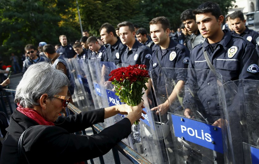 A demonstrator holds flowers before a police barricade during a commemoration for the victims of Saturday's bomb blasts in the Turkish capital, in Ankara, Turkey, October 11, 2015. Photo: Reuters/Umit Bektas