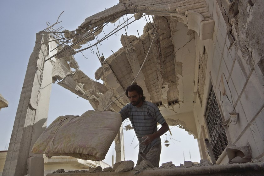A man removes belongings from his damaged house that was hit by what activists said was a barrel bomb dropped by forces loyal to Syria's President Bashar al-Assad in the town of al-Ghariyah al-Gharbiyah in Deraa province, Syria on October 12, 2015. Photo: Reuters/Alaa Al-Faqir