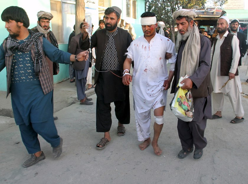 A wounded man is being helped after a rocket attack by Taliban in the city of Ghazni, Afghanistan, October 13, 2015. Photo: Reuters