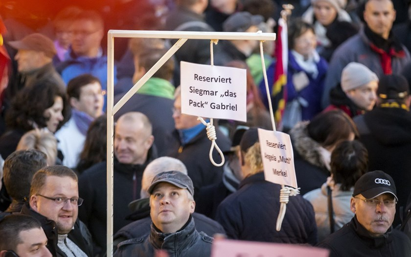People hold up a mock hangman's gallows with a sign reading 'Reserved for Sigmar Gabriel' (L) and 'Reserved for Angela Merkel' as they gather for an anti-immigration demonstration organised by rightwing movement Patriotic Europeans Against the Islamization of the West (PEGIDA) in front of the Palace Church in Dresden, Germany October 12, 2015. Photo: Reuters/Hannibal Hanschke