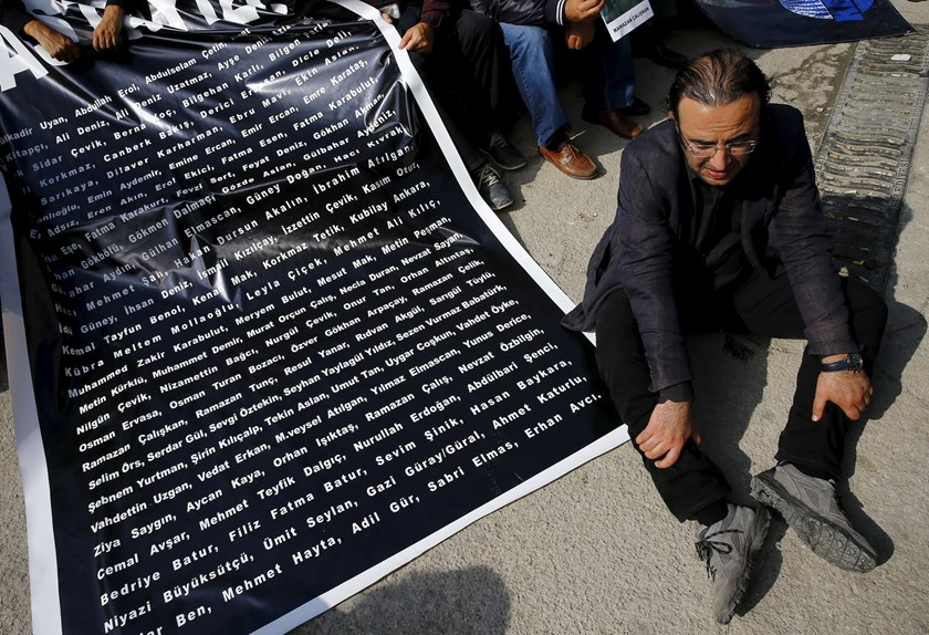 A man sits next to a banner with names of those killed by Saturday's suicide bombings as they attend a commemoration in Ankara, Turkey, October 13, 2015. Photo: Reuters/Umit Bektas