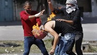 Palestinian protesters put out a fire burning on a compatriot, caused by a molotov cocktail which he was trying to hurl at Israeli troops during clashes in the West Bank city of Hebron, October 13, 2015. Photo: Reuters/Mussa Qawasma