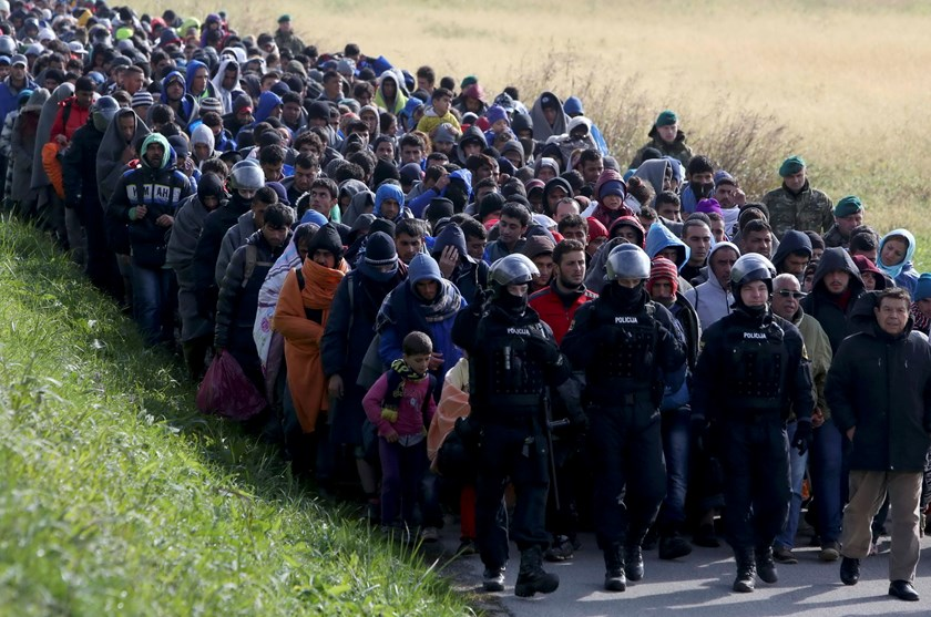 Policemen lead a group of migrants near Dobova, Slovenia October 20, 2015. Migrants continue to stream north through the Balkans from Greece but Hungary sealed its border with Croatia on Friday and Slovenia imposed daily limits on migrants entering from Croatia, leaving thousands stuck on cold, rain-sodden frontiers. Photo: Reuters/Srdjan Zivulovic