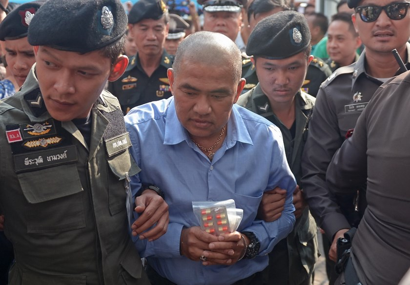 Thai fortune teller Suriyan Sucharitpholwong (C), 54, also known as Mor Yong, is escorted by commando police during his arrival at a military court in Bangkok on October 21, 2015. Photo: AFP/Pornchai Kittiwongsakul