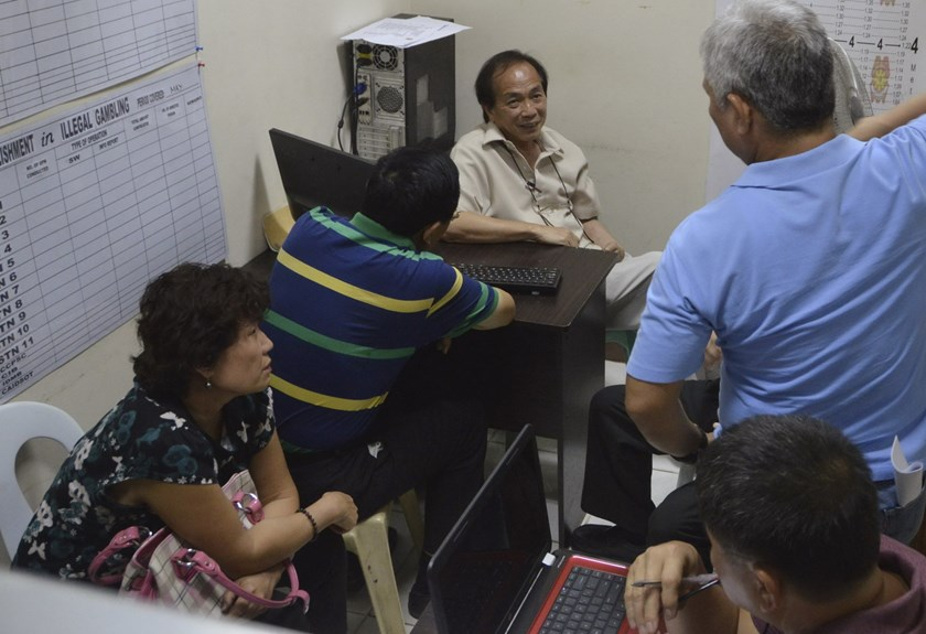 Li Qingliang (2nd L), the suspect in a shooting of three Chinese diplomats, sits near his wife Guo Jing as he is questioned by police at a police station in Cebu city, central Philippines October 21, 2015. Photo: Reuters/Alan Tangcawan