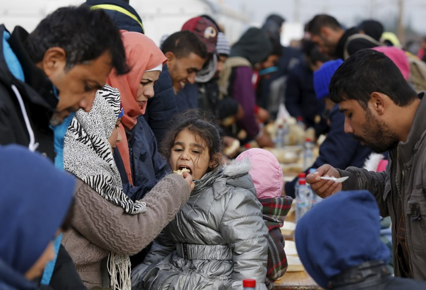 Migrants eat a warm meal delivered by humanitarian organizations on their way to the border with Serbia after arriving by train at Tabanovce, Macedonia October 24, 2015. Photo: Reuters/Ognen Teofilovski