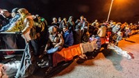 """Refugees wait in line on the Innbruecke bridge at the German/Austrian border at Simbach am Inn, southern Germany on October 25, 2015. Germany faced a new influx of migrants in Bavaria on the border to Austria, where police said to be """"overwhelmed"""" with the number of refugees who flocked during the weekend. Photo: AFP /DPA/Armin Weige"""