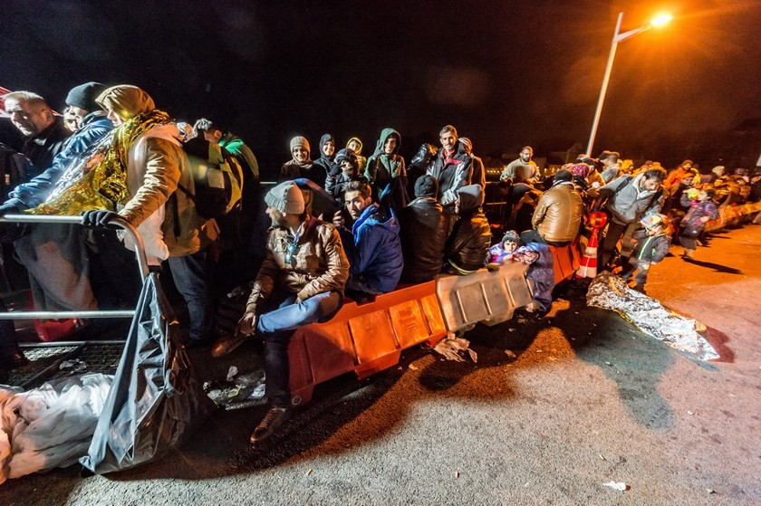 "Refugees wait in line on the Innbruecke bridge at the German/Austrian border at Simbach am Inn, southern Germany on October 25, 2015. Germany faced a new influx of migrants in Bavaria on the border to Austria, where police said to be ""overwhelmed"" with the number of refugees who flocked during the weekend. Photo: AFP /DPA/Armin Weige"