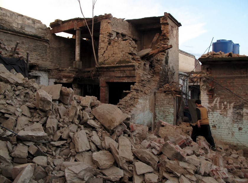 A resident walks past the rubble of a house after it was damaged by an earthquake in Mingora, Swat, Pakistan, October 26, 2015. Photo: Reuters/Hazrat Ali Bacha