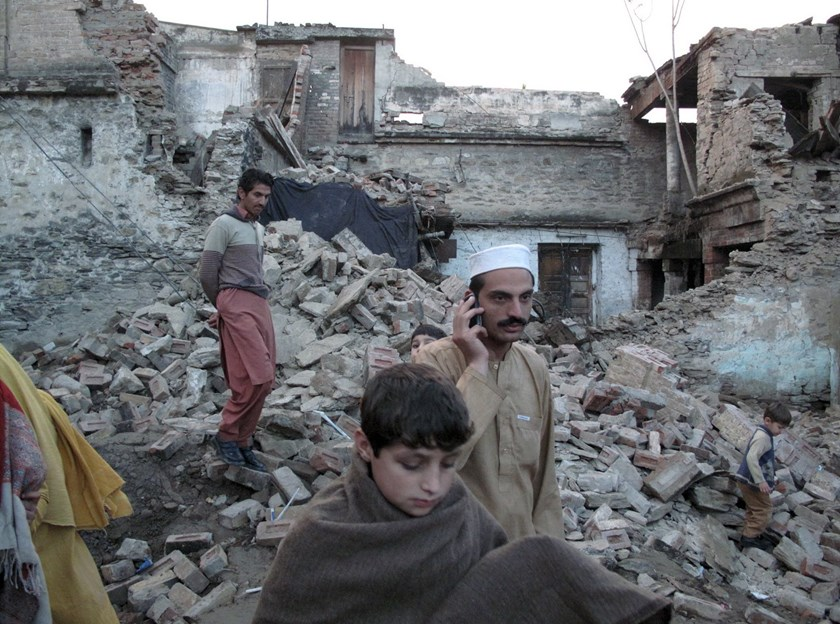 Residents walk past the rubble of a house after it was damaged by an earthquake in Mingora, Swat, Pakistan, October 26, 2015. Photo: Reuters/Hazrat Ali Bacha