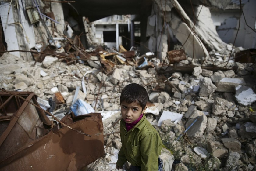 A boy walks amid damaged buildings in the town of Douma, eastern Ghouta in Damascus, Syria October 26, 2015. Photo: Reuters/Bassam Khabieh