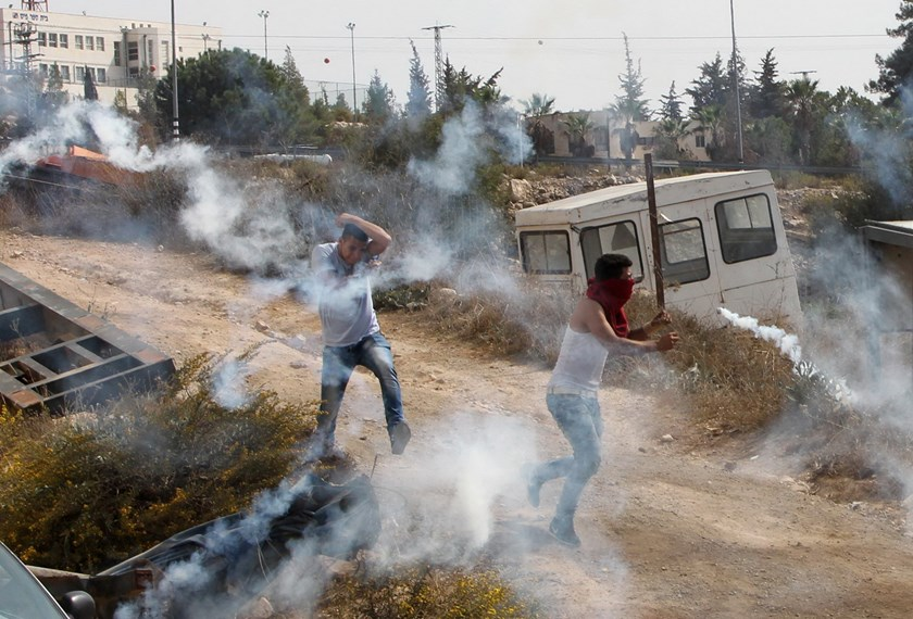 Palestinian students from Palestine Polytechnic University react as tear gas canisters are fired by Israeli security forces during clashes following a protest against Israel near the Jewish settlement of Beit Hagai, at the southern entrance to the occupied West Bank city of Hebron, on October 18,2015. Photo: AFP/Hazem Bader