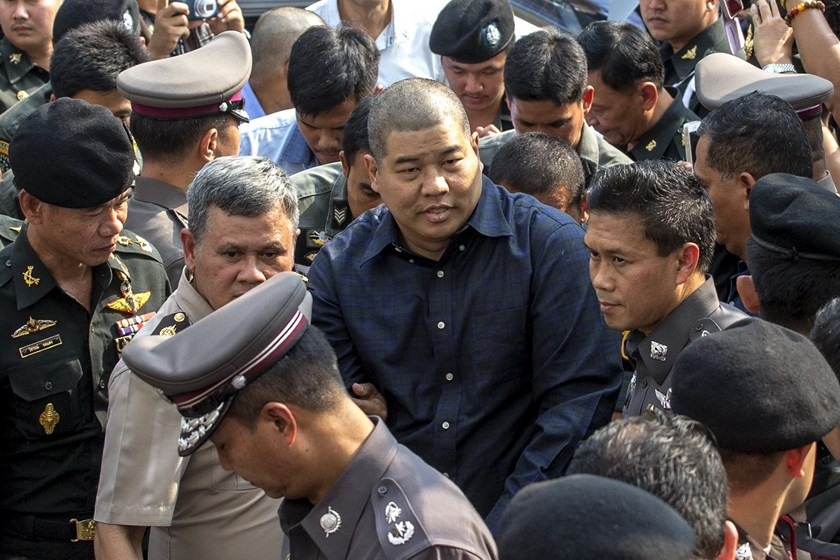 Police Major Prakrom Warunprapa, lese-majeste suspect (C) is escorted by police officer as he arrives at military court in Bangkok, Thailand, October 21, 2015. Warunprapa, who was under investigation as part of a high profile royal insult probe, died in custody on October 23 after he hanged himself in his cell. Photo: Reuters/Athit Perawongmetha