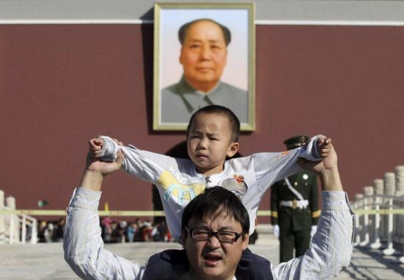 A boy sits on his father's shoulders as they pose for a photograph in front of the giant portrait of late Chinese chairman Mao Zedong on the Tiananmen Gate, in Beijing, China, October 2, 2011. Photo: Reuters