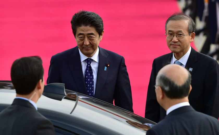 Japanese Prime Minister Shinzo Abe (C) arrives as South Korean First Vice Foreign Minister Lim Sung-Nam (R) welcomes him at Seoul air base in Seongnam, south of Seoul, on November 1, 2015. Abe arrived in South Korea ahead of a trilateral leadership summit with South Korea and China. Photo: AFP/Jung Yeon-Je