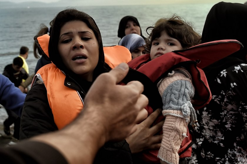 A woman holding her child, arrives, along with other refugees and migrants, on the Greek island of Lesbos, on November 10, 2015, after crossing the Aegean Sea from Turkey. Photo: AFP/Aris Messinis