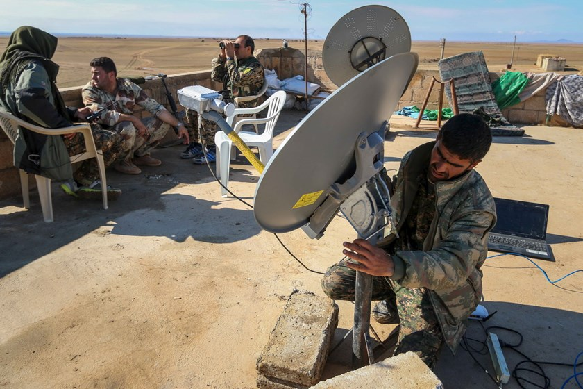 Rebel fighters form the Democratic Forces of Syria, sit on a rooftop as one of them fixes the direction of a satellite near al-Hawl area where fighting between them and Islamic State fighters are taking place in south-eastern city of Hasaka, Syria November 10, 2015. Photo: Reuters/Rodi Said