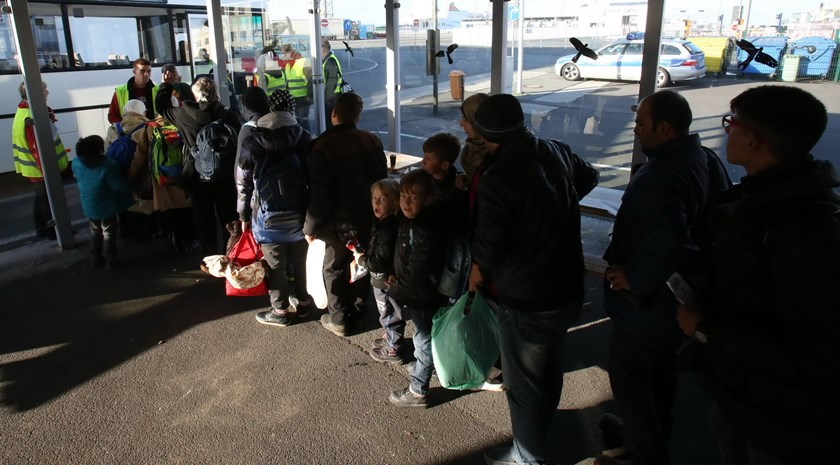 Migrants enter a bus that will bring them to the ferry for their passage to Sweden on November 12, 2015 at the port of Rostock, northeastern Germany, where refugees in transit wait to continue their trip through Europe. Photo: AFP/DPA/ Bernd Wuestneck