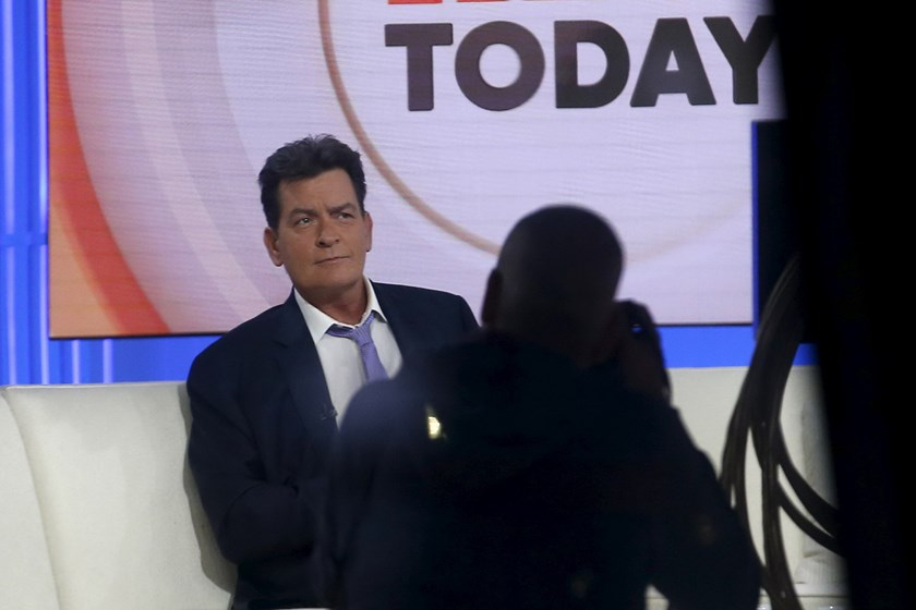 Actor Charlie Sheen is seen through a window as he sits on the set of the NBC Today show prior to being interviewed by host Matt Lauer in the Manhattan borough of New York City, November 17, 2015. Photo: Reuters/Mike Segar