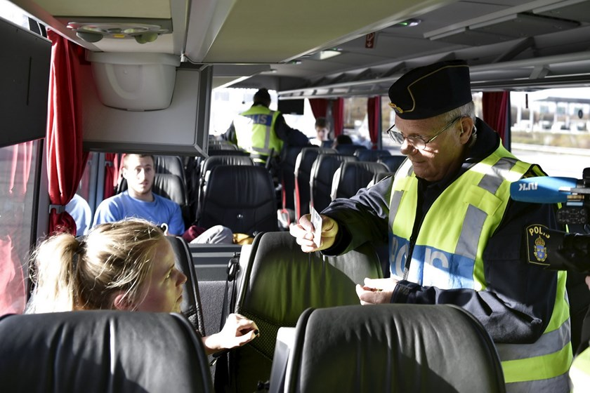 A police officer checks passports inside a bus at Lernacken, on the Swedish side of the Oresund strait, November 12, 2015. REUTERS/Nils Meilvang/Scanpix