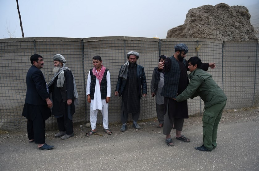 In this photograph taken on October 19, 2015 an Afghan security personnel searches commuters as others look on at a checkpoint in Maimana, the capital of the northern province of Faryab. Photo: AFP/Wakil KOHSAR
