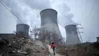 A girl makes her way to her house next to cooling towers of a coal-fired power plant in Shijiazhuang, Hebei province, China, in this January 28, 2015 file photo. Photo: Reuters/Kim Kyung-Hoon/Files