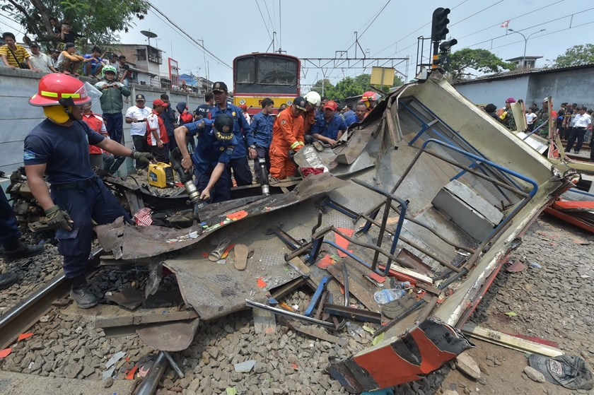 Indonesian firefighters cut the wreckage of a minibus after it collided with a train in Jakarta on December 6, 2015. Photo: AFP/Adek Berry