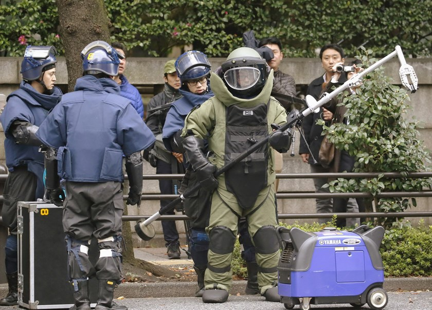 Members of a police bomb disposal squad wearing blast protection equipments prepare to work near the site of an explosion at the Yasukuni shrine in Tokyo, in this photo taken by Kyodo November 23, 2015 file photo. Photo credit: Reuters/Kyodo/Files