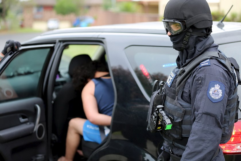 Heavily armed police officers detain a man during early morning raids in western Sydney, Australia, December 10, 2015, in this handout courtesy of New South Wales (NSW) Police. Photo: Reuters/NSW Police/Handout via Reuters