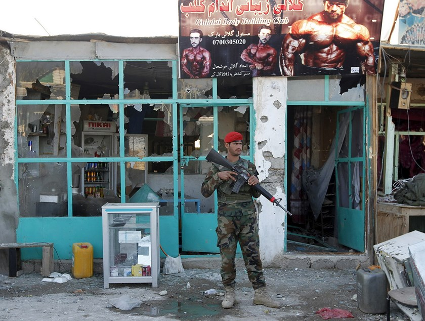 Afghan National Army (ANA) soldiers stand guard in front of a shop burned during the Taliban attack on Kandahar Airport in Kandahar, December 9, 2015. Photo: Reuters
