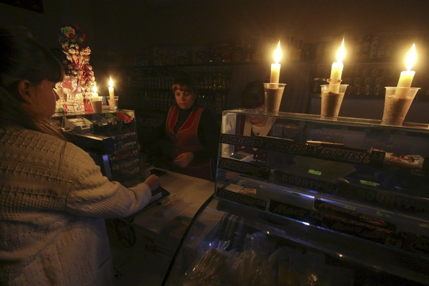 A customer visits a grocery lit with candles due to a power cut, in Simferopol, Crimea, in this November 22, 2015 file photo. Photo: Reuters/Pavel Rebrov/Files