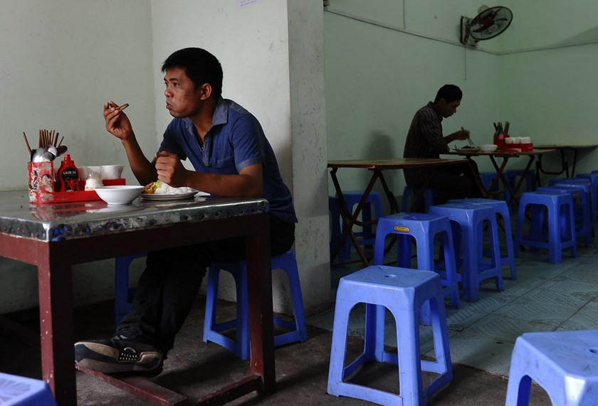 This picture taken on September 21, 2015 shows two migrant workers having lunch at a small restaurant run by migrants Le Van Mung and Ngoc Anh (not pictured) in Hanoi. Some 7.5 million people moved to Vietnam's cities between 2000 and 2010, according to World Bank figures, an urbanization rate of 4.1 percent. Photo: Hoang Dinh Nam/AFP