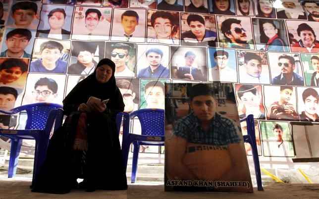 Shahana Ajoon, mother of Asfand Khan, sits beside a picture of her son in Peshawar, Pakistan December 11, 2015. Photo: Reuters/Caren Firouz