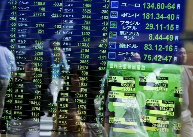 Passersby are reflected on a screen displaying stock quotation, the stock market indices of various countries (bottom R) and exchange rates (top R) at a brokerage in Tokyo, Japan, September 29, 2015.