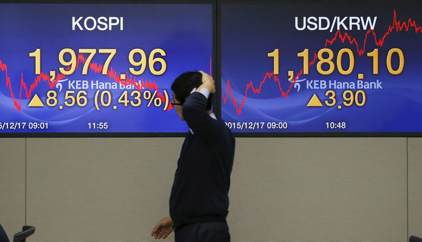 A currency dealer walks in front of electronic boards showing the Korea Composite Stock Price Index (KOSPI) and the exchange rate between the U.S. dollar and South Korean won, at a dealing room of a bank in Seoul, South Korea, December 17, 2015. Reuters/Kim Hong-Ji
