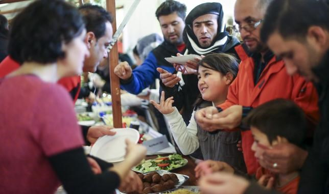 Migrants receive food at a Christmas market in a refugee shelter run by German charity organization Arbeiter Samariter Bund ASB in Berlin, Germany, December 12, 2015. Photo:Reuters/Hannibal Hanschke