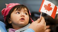 A young Syrian refugee looks up as her father holds her and a Canadian flag at the as they arrive at Pearson Toronto International Airport in Mississauga, Ontario, December 18, 2015. Photo: Reuters/Mark Blinch